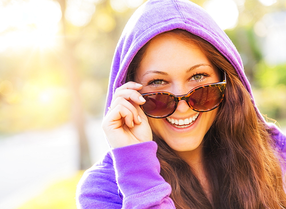 Portrait of smiling woman in hoodie with sunglasses, Jupiter, Florida