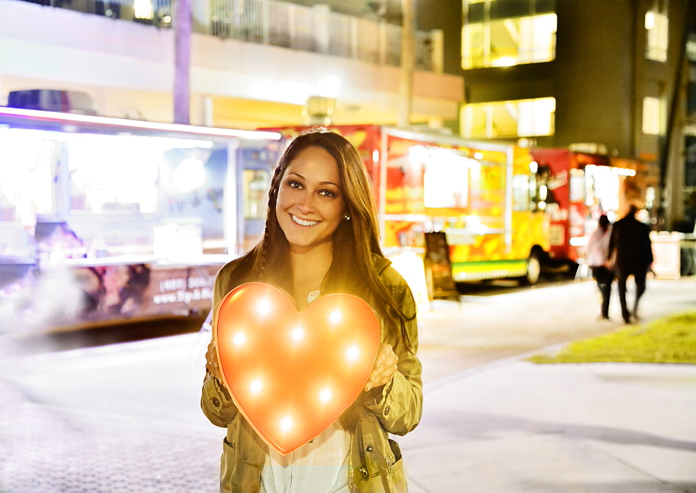Woman in front of building and food truck holding illuminated heart, Jupiter, Florida