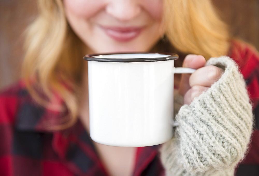 Woman holding metal coffee mug