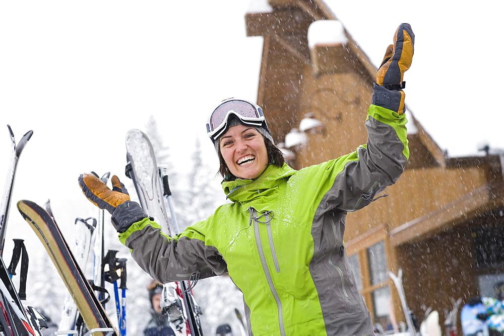 Woman wearing ski googles with hands raised, Whitefish, Montana, USA