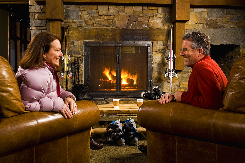 Man and woman chatting in front of fireplace, Whitefish, Montana, USA
