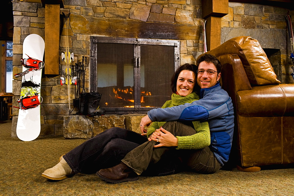 Man and woman hanging out in front of fireplace, Whitefish, Montana, USA