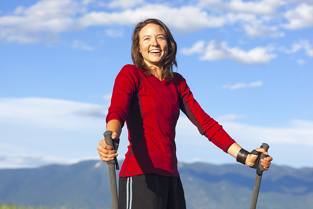 Portrait of smiling woman with trekking poles, Whitefish, Montana, USA