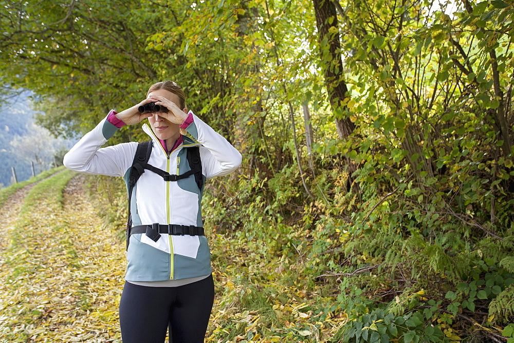 Woman looking through binoculars, Austria, Salzburger Land, Maria Alm
