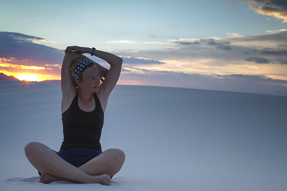Mid-adult woman doing yoga in desert, White Sands National Monument, Alamogordo, New Mexico