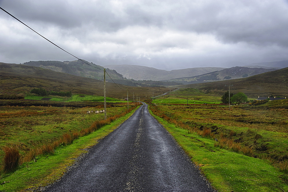 Landscape with asphalt road and green grass, clouds in sky, hills in background, Rural County Mayo, Ireland