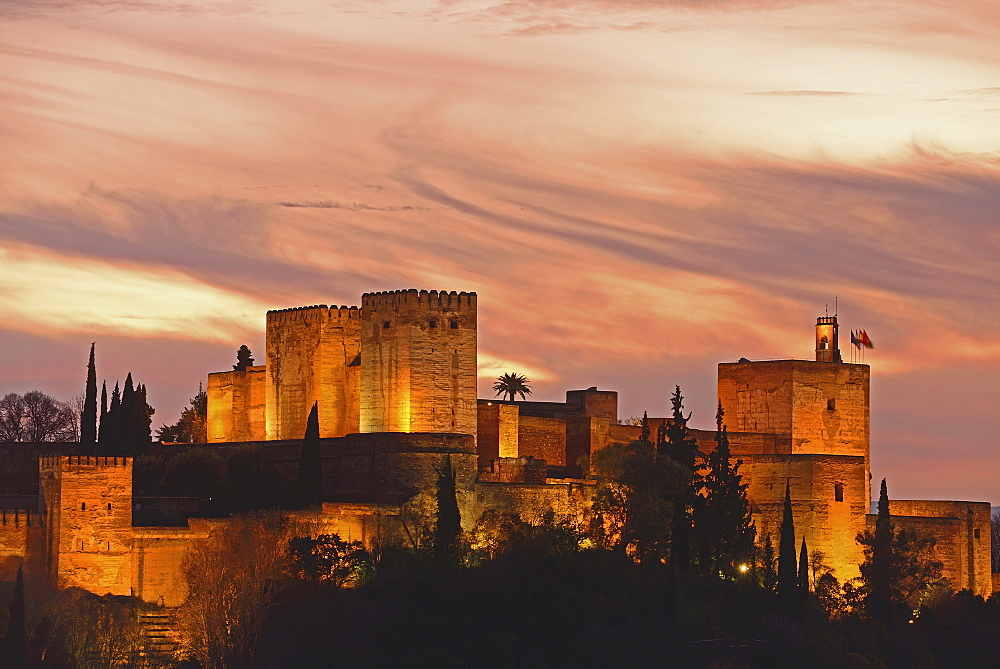 Illuminated castle at dusk, pastel colored clouds in sky, Alhambra, Granada, Spain