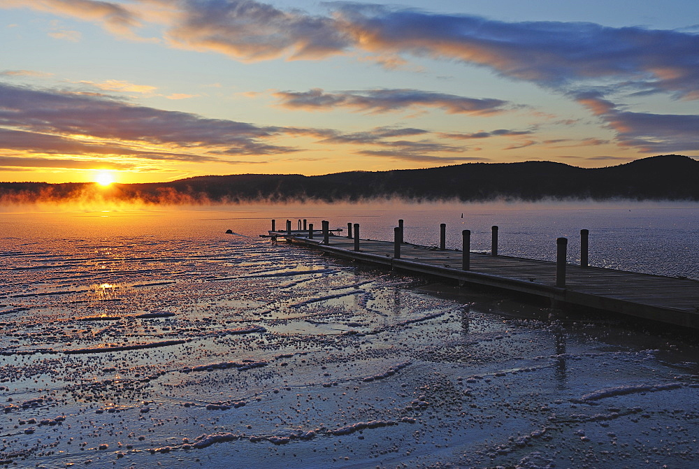 Jetty on frozen lake, hills in background at sunrise, Lake George, New York