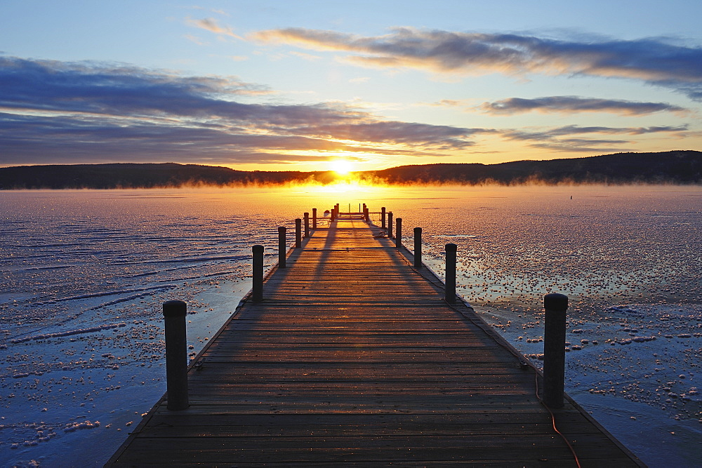 Symmetrical view of jetty on frozen lake, hills in background at sunrise, Lake George, New York
