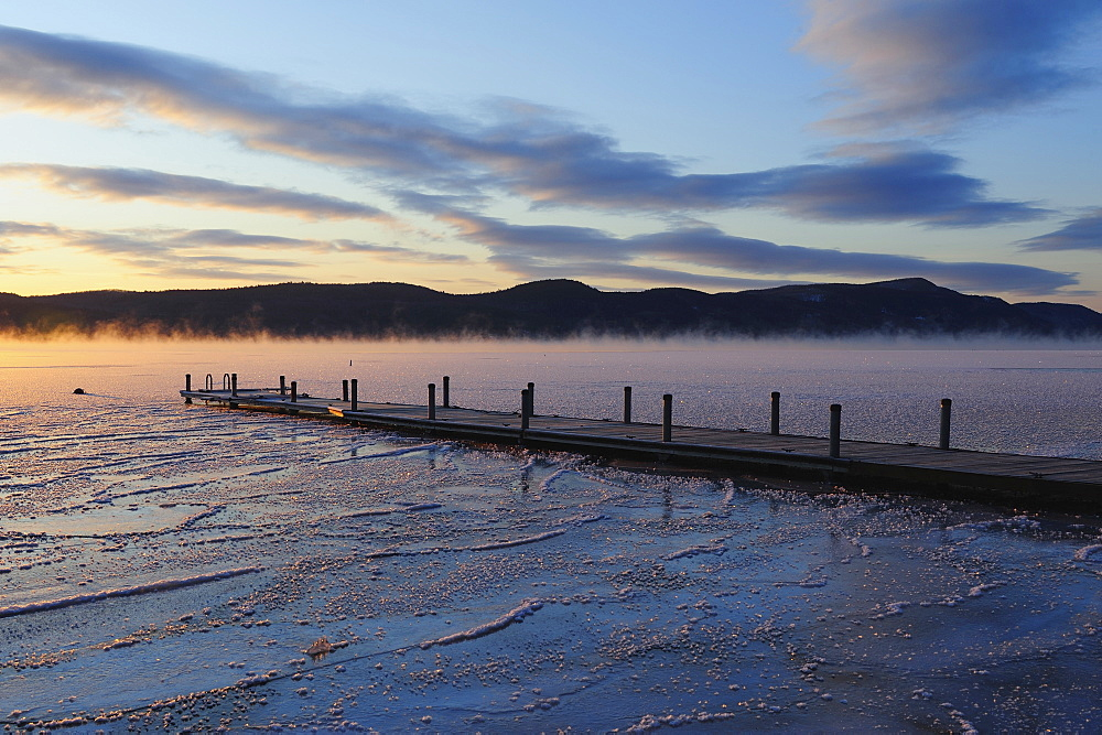 Jetty on frozen lake with vapor, hills in background at sunrise, Lake George, New York
