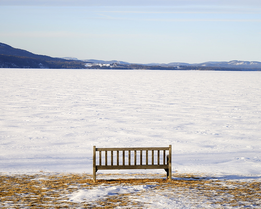 Park bench at edge of a frozen snowed lake, hills in background, Crown Point, New York