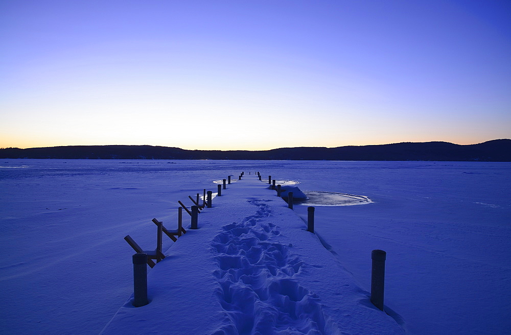 Symmetrical image of snowed jetty with footprints at dawn, hills on horizon, Lake George, New York - 1178-24687