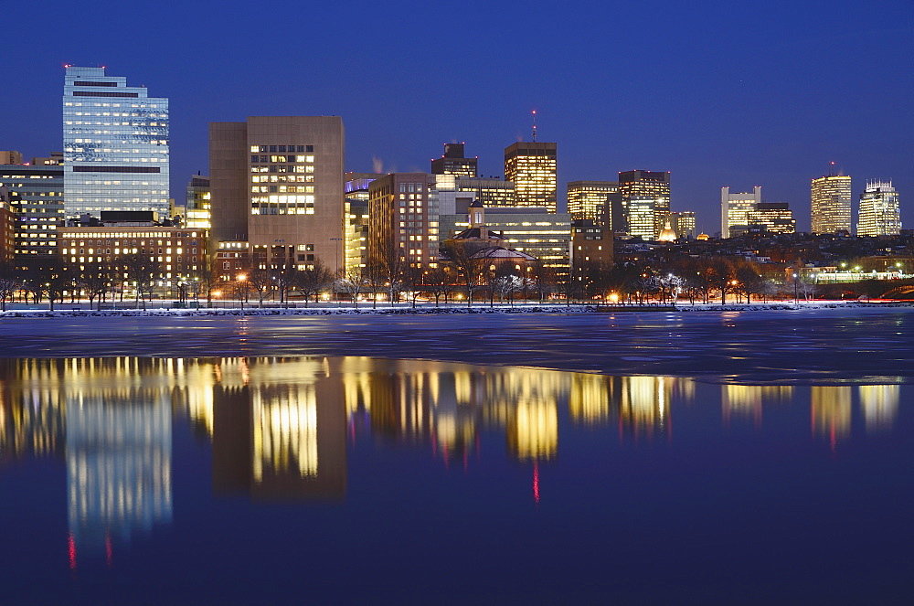 Illuminated cityscape reflecting in water at dusk, Boston, Massachusetts