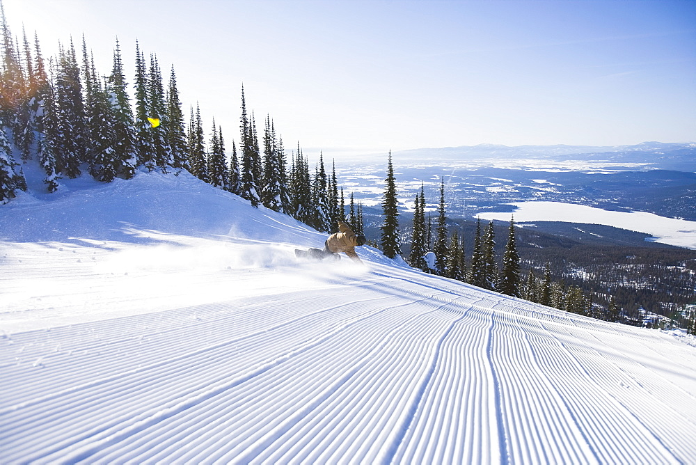 Snowboarder on side of ski slope, Whitefish, Montana, USA