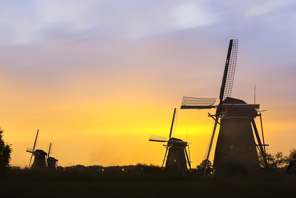 Winmills silhouetted against sunset sky, Kinderdijk, South Holland, Netherlands