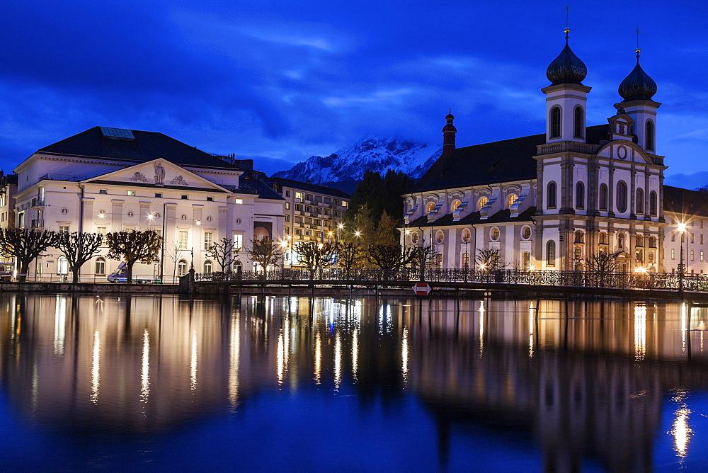 Illuminated building reflecting in lake, Lucerne, Switzerland
