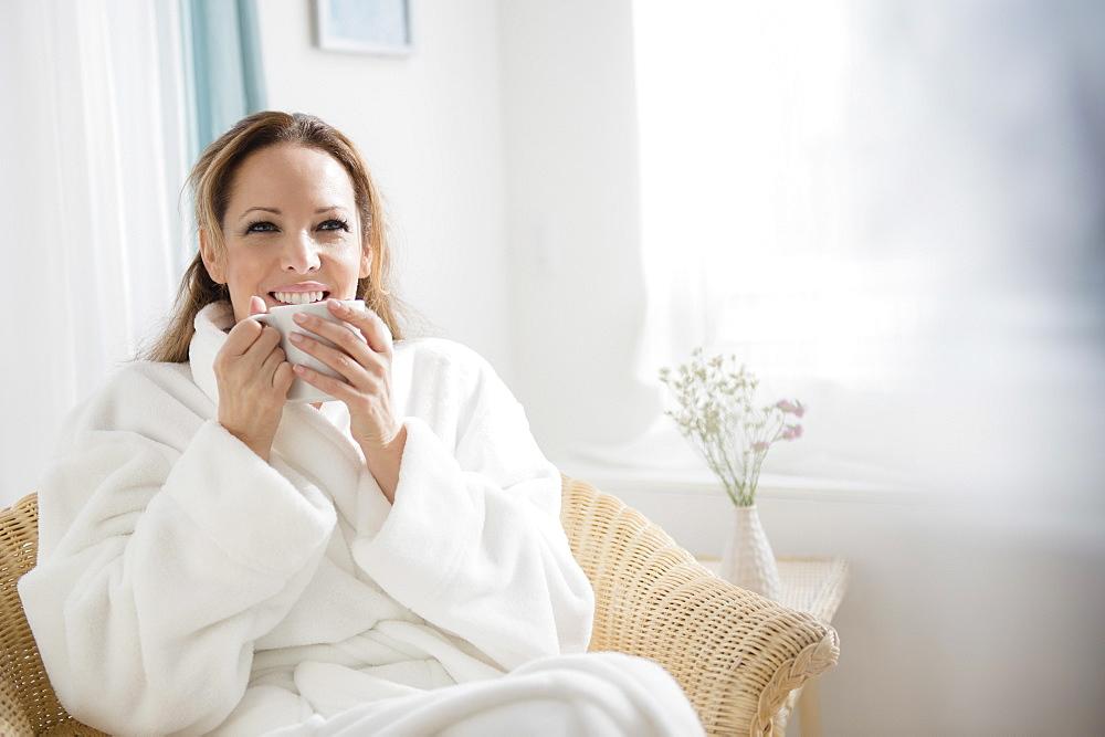 Woman wearing bathrobe drinking tea
