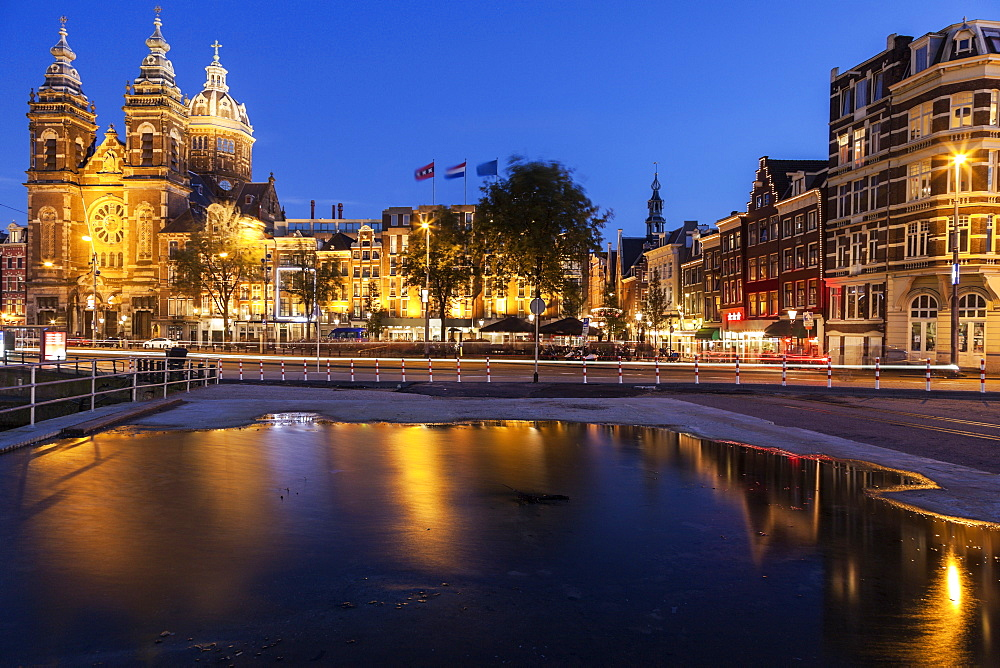 Canal and illuminated buildings at sunrise, Amsterdam, North Holland, Netherlands