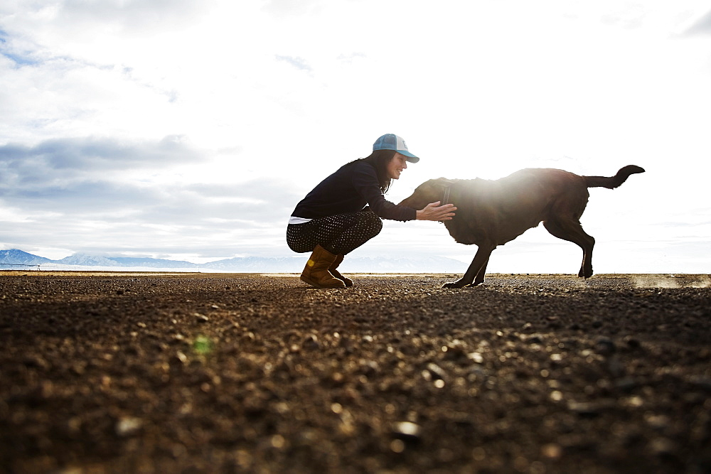 Woman with dog outdoors at sunrise, Colorado, USA
