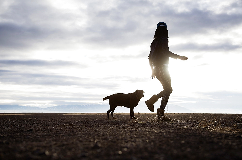 Woman walking with dog at sunrise, Colorado, USA