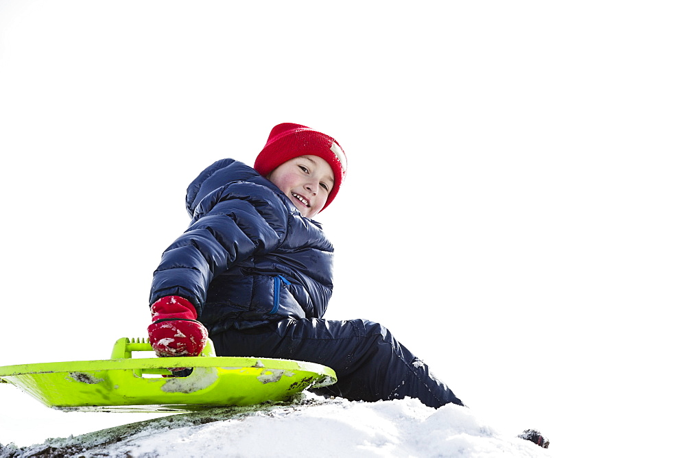 Boy (6-7) sledding in winter