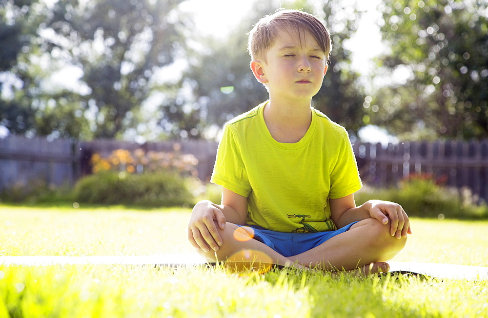 Boy (6-7) sitting in grass, Colorado, USA