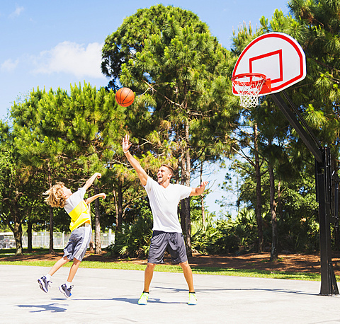 Boy (8-9) playing basketball with his brother