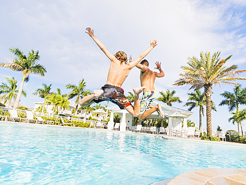 Boy (8-9) diving into swimming pool with his brother, Florida,USA
