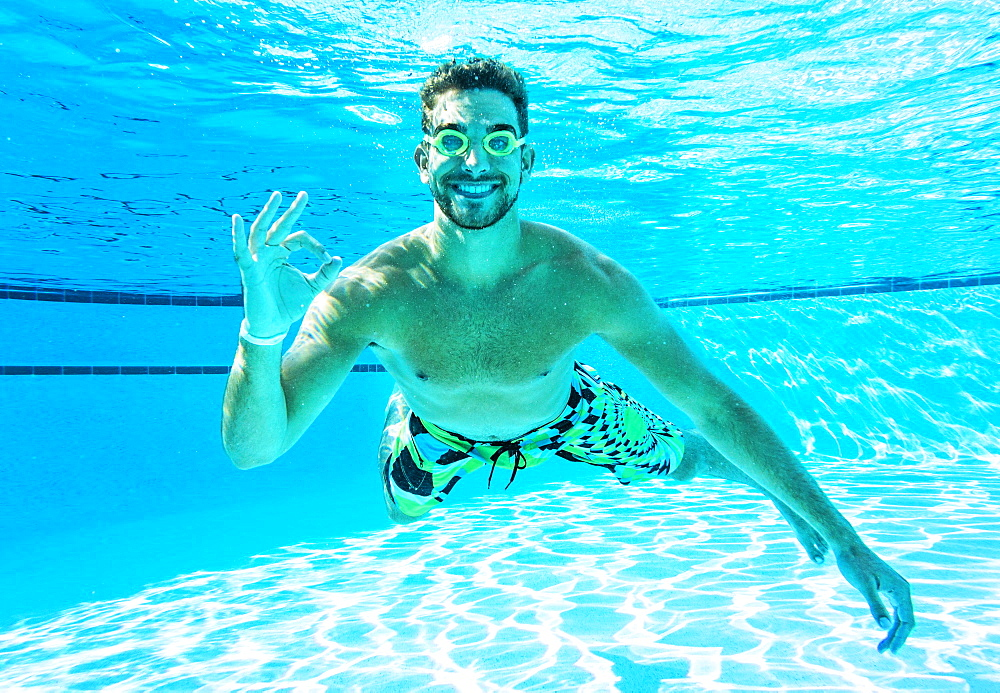 Young man doing ok sign in swimming pool, Florida,USA