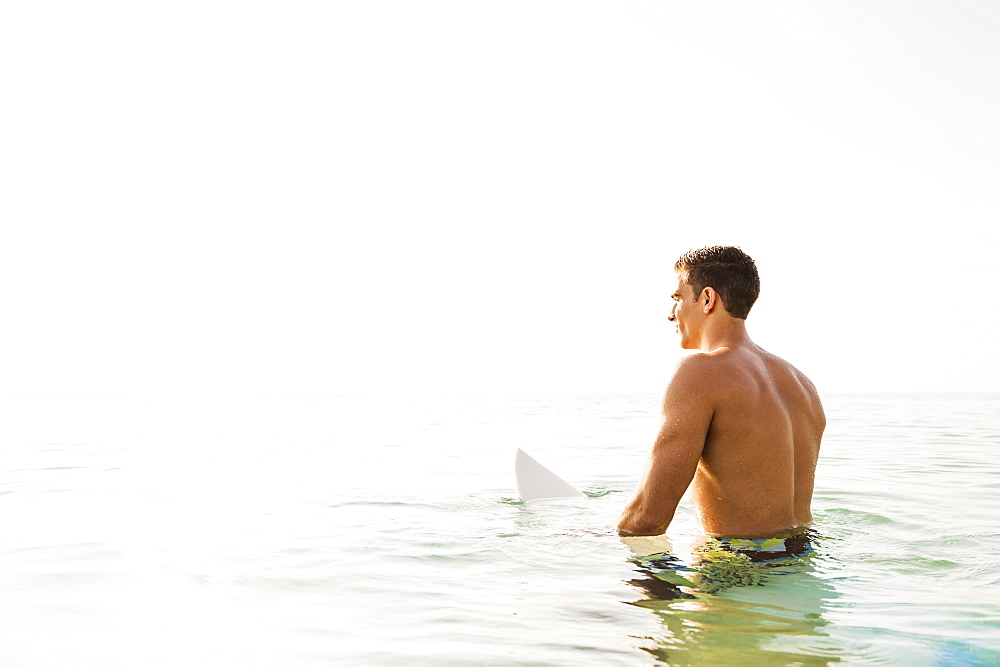 Young surfer watching waves, West Palm Beach, Florida,USA