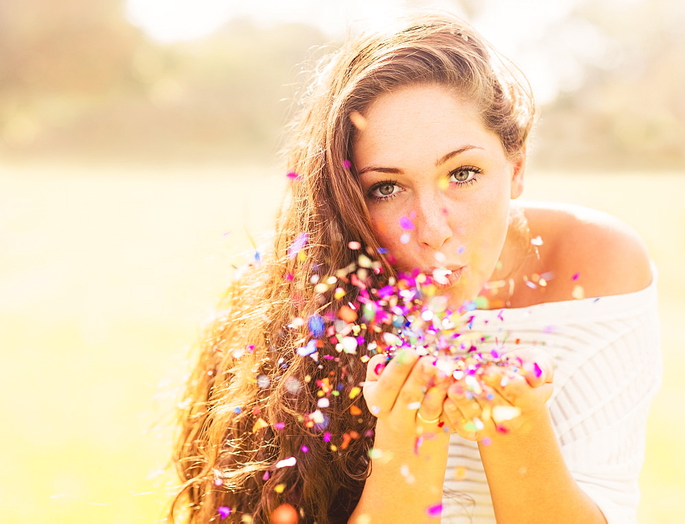 Young woman blowing confetti, Jupiter, Florida,USA