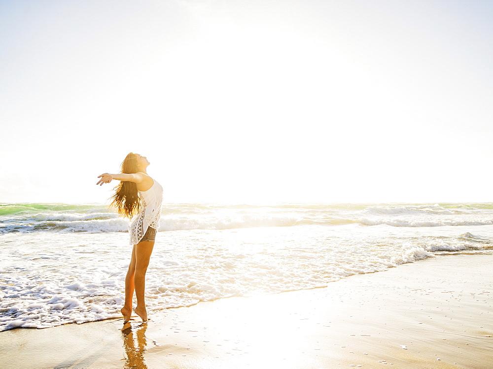 Woman on beach with arms raised, Jupiter, Florida,USA