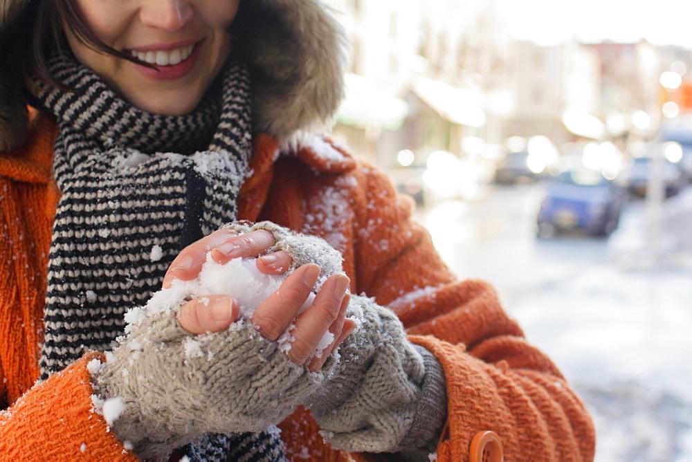 Woman making snowball in street, Brooklyn, New York,USA