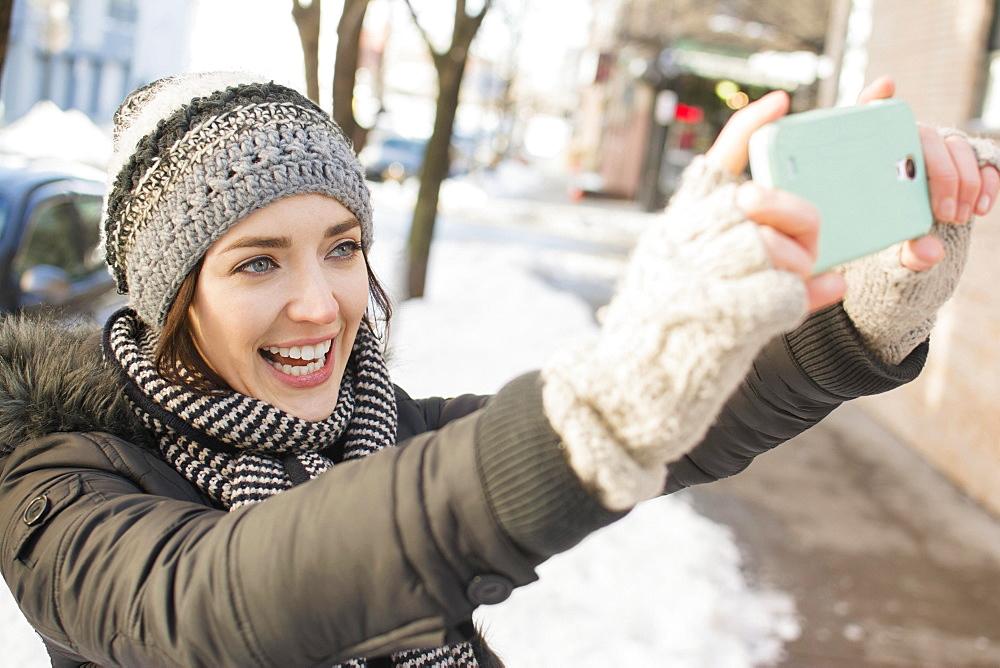 Woman in street taking selfie, Brooklyn, New York,USA