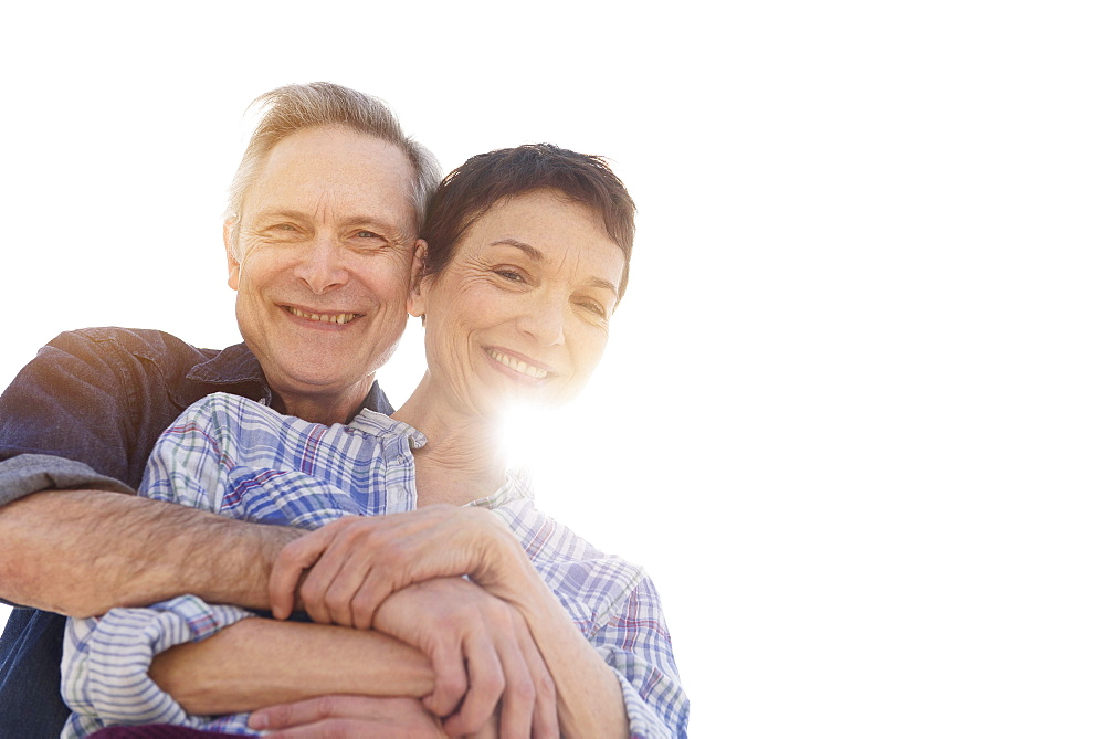 Portrait of smiling senior couple embracing in sunlight