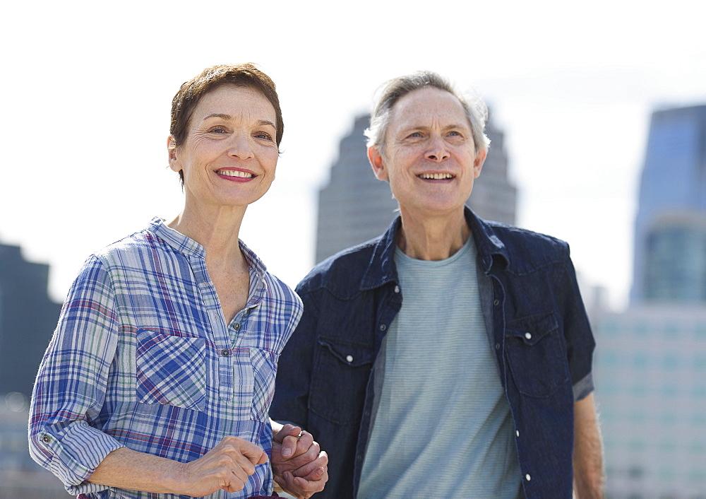Smiling senior couple walking in city