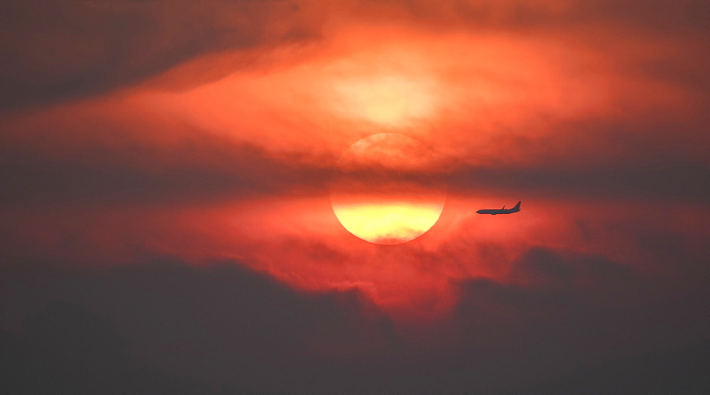 Silhouette of airplane against setting sun