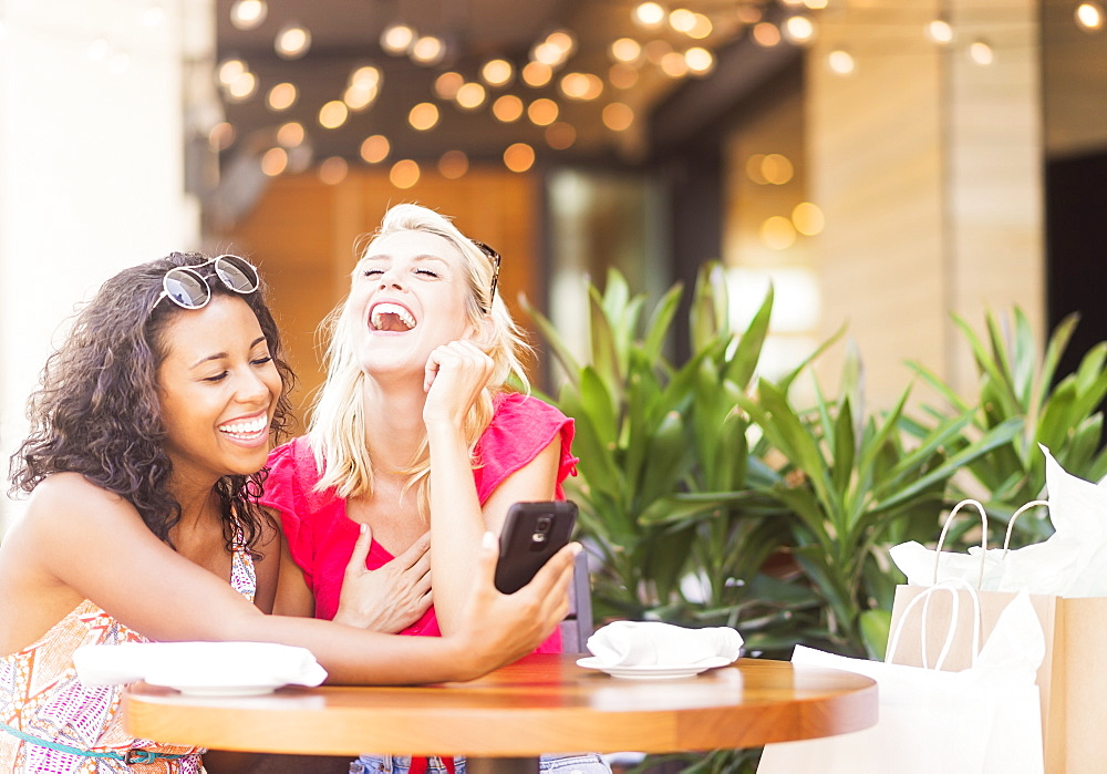 Female friends using smart phone in cafe