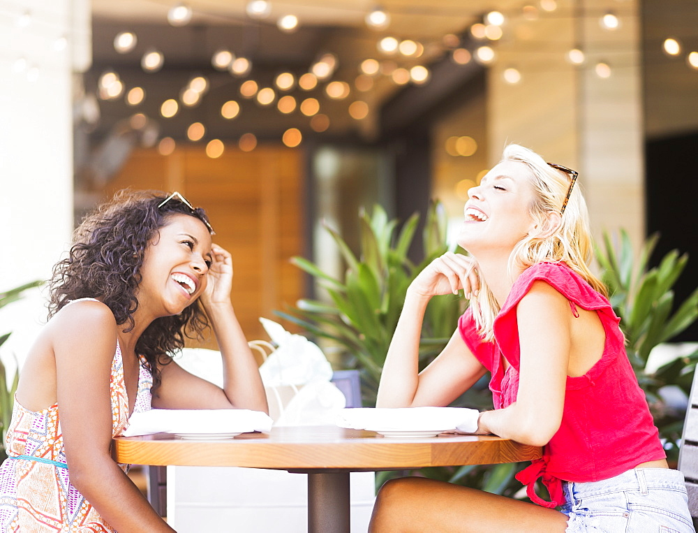 Female friends laughing in street cafe
