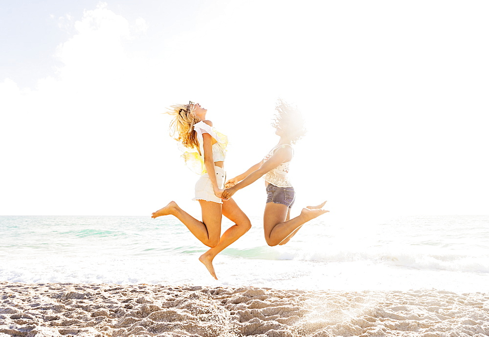 Female friends jumping on beach, USA, Florida, Jupiter - 1178-25074