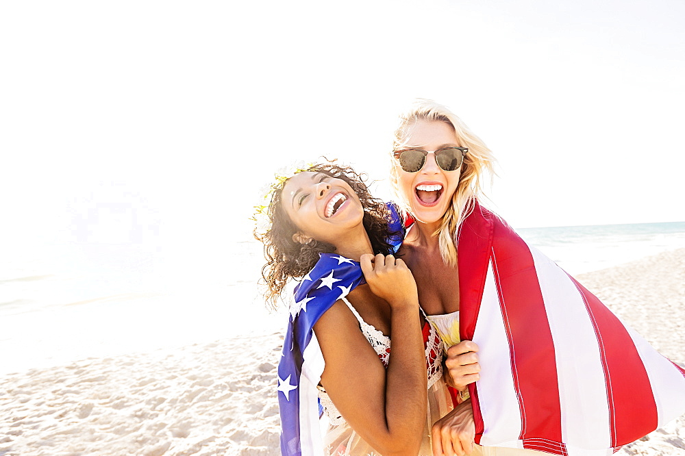 Female friends on beach with American flag, USA, Florida, Jupiter