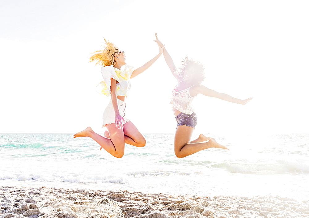 Female friends jumping on beach, USA, Florida, Jupiter