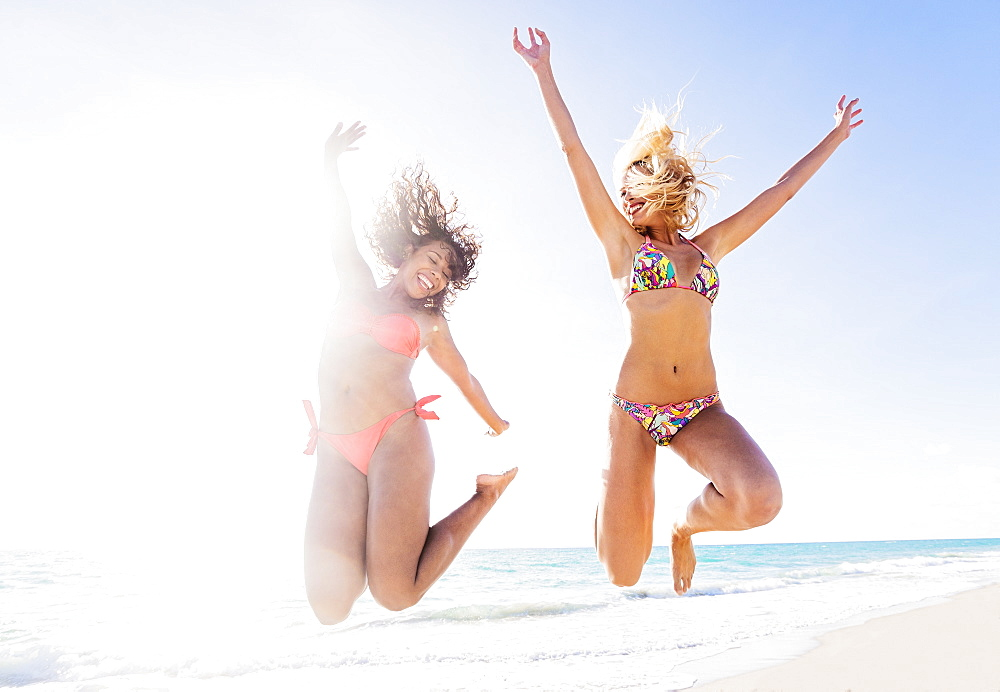 Female friends jumping on beach, USA, Florida, Jupiter