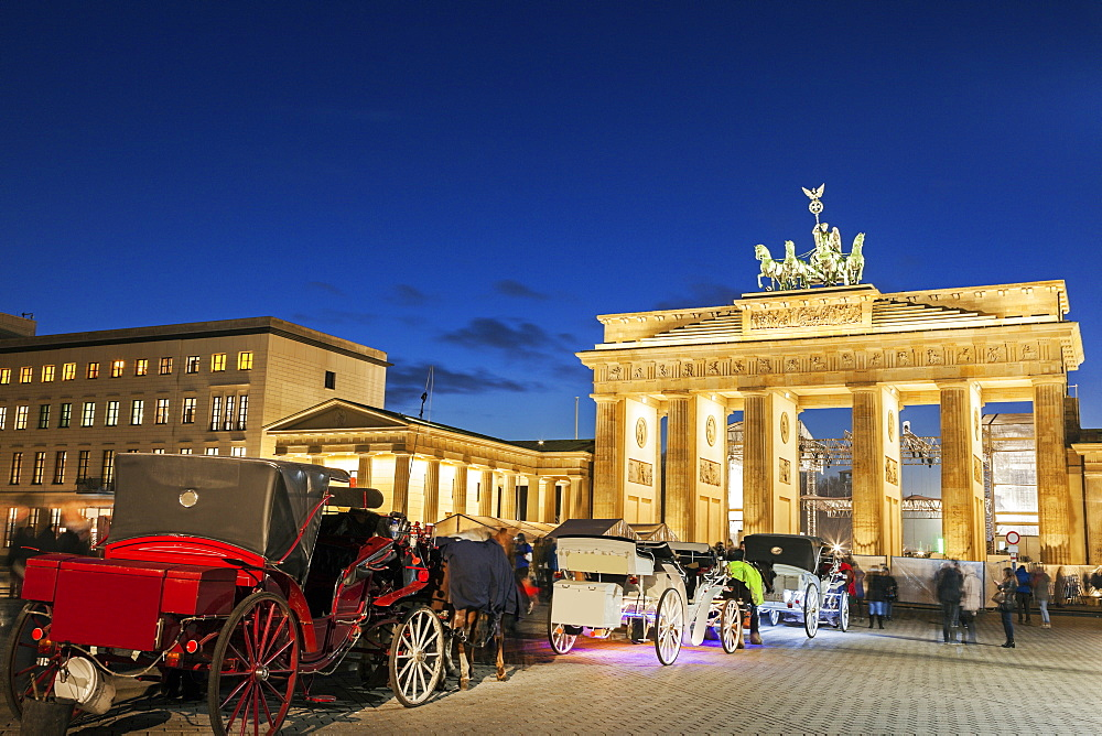 Horse carts in front of illuminated Brandenburg Gate, Germany, Berlin, Brandenburg Gate