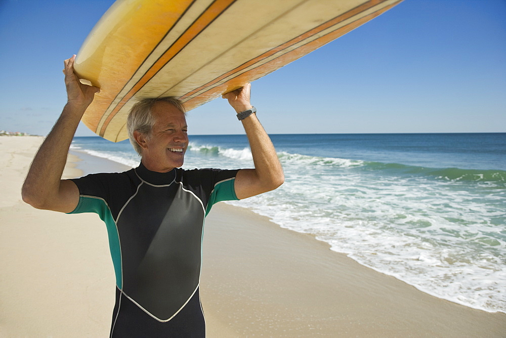 Man holding surfboard at beach