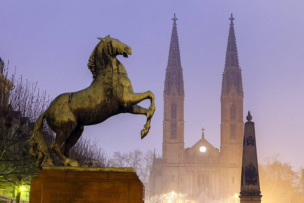Horse sculpture of Waterloo Memorial and St. Boniface Church in mist, Germany, Hesse, Waterloo Memorial on Luisenplatz, St. Boniface Church