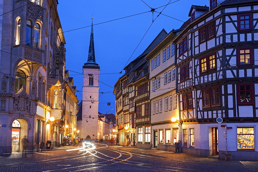 Illuminated city street and Allerheiligenkirche bell tower, Germany, Thuringia, Erfurt, Allerheiligenkirche