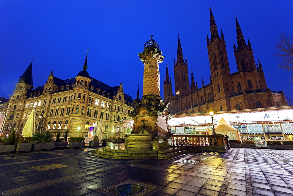 Monument on illuminated square, Germany, Hesse, Wiesbaden, Rathaus and Marktkirche