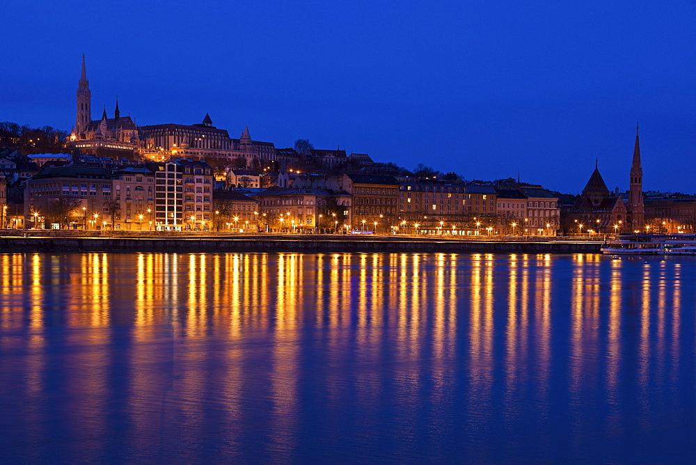 Illuminated skyline reflecting in Danube River, Hungary, Budapest, Matthias Church,Fisherman's Bastion, Danube River