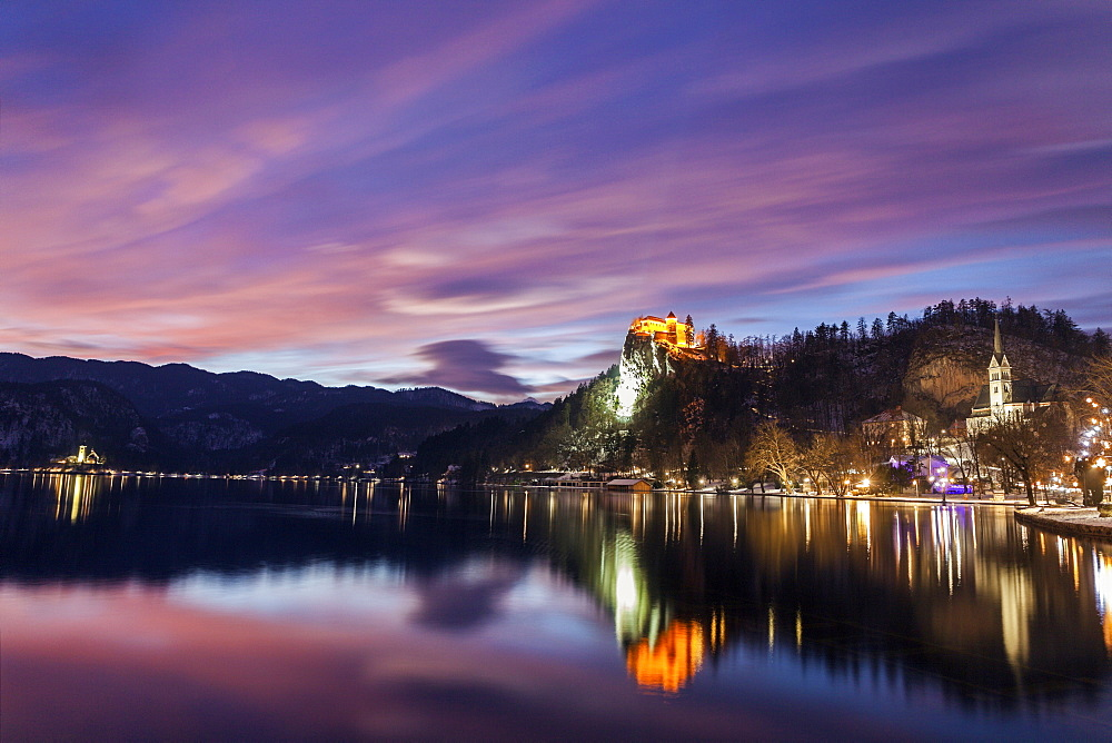Lake Bled and illuminated Church of the Assumption reflecting in lake, Slovenia, Bled